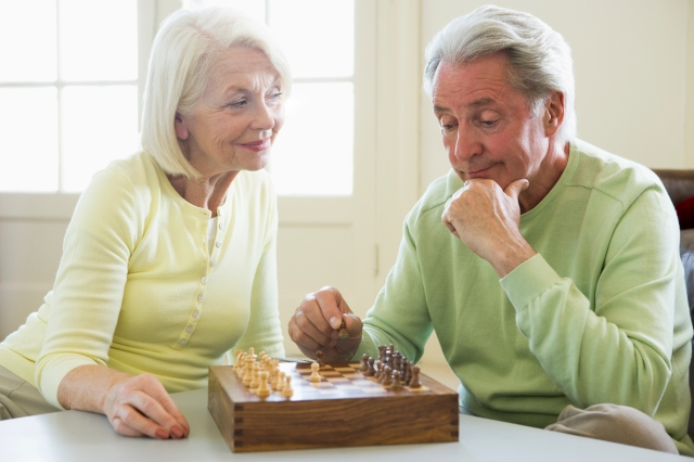 Couple playing chess in living room smiling